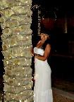 Frau in weißem Kleid lehnt sich gegen eine Mauer